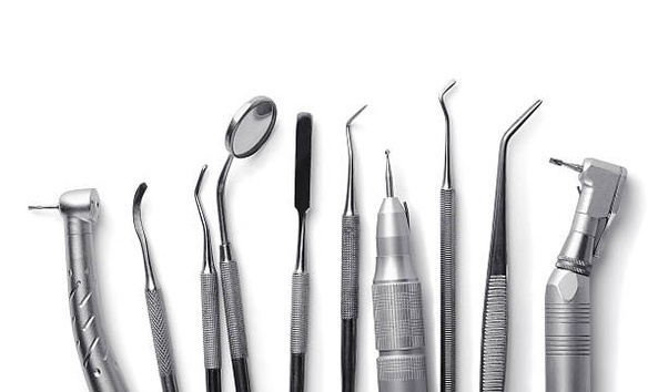 a row of tools used by a dentist (mirror, probes, drills)